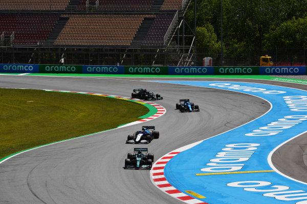 Lance Stroll, Aston Martin AMR21, leads Nicholas Latifi, Williams FW43B, Fernando Alonso, Alpine A521, and Sir Lewis Hamilton, Mercedes W12