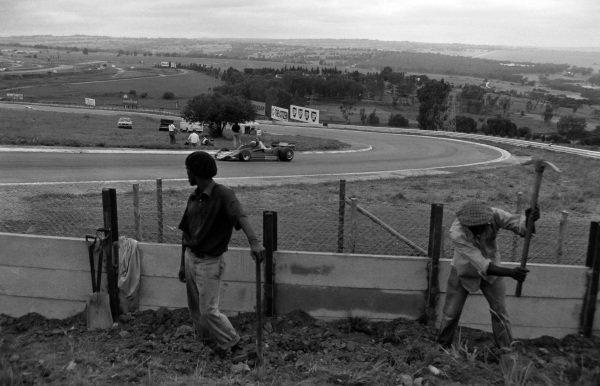 John Watson, Brabham BT45 Alfa Romeo, passes two men hard at work.