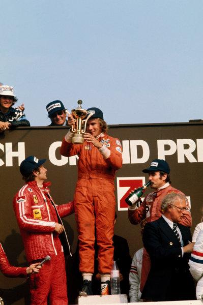 Zandvoort, Holland. 20 - 22 June 1975. James Hunt (Hesketh 308-Ford), 1st position, with Niki Lauda (Ferrari 312T), 2nd position and Clay Regazzoni (Ferrari 312T),3rd position on the podium, portrait.  World Copyright: LAT Photographic. Ref:  75HOL11.