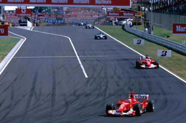 2004 Hungarian Grand Prix Hungaroring, Hungary. 13th - 15th August. Michael Schumacher, Ferrari F2004 leads team mate Rubens Barrichello, Ferrari F2004. Action. World Copyright:Charles Coates/LAT Photographic Ref:35mm Image:A05