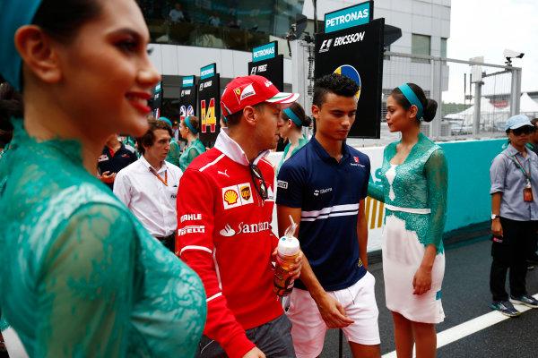 Sepang International Circuit, Sepang, Malaysia. Sunday 01 October 2017. Sebastian Vettel, Ferrari, and Pascal Wehrlein, Sauber, walks through a corridor of grid girls. World Copyright: Andy Hone/LAT Images  ref: Digital Image _ONY4456