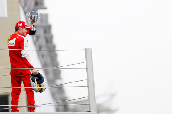 Interlagos, Sao Paulo, Brazil. Sunday 15 November 2015. Sebastian Vettel, Ferrari, 3rd Position, with his trophy on the podium. World Copyright: Alastair Staley/LAT Photographic ref: Digital Image _79P5879