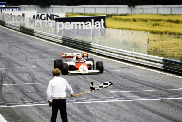 Niki Lauda, McLaren MP4-2 TAG, crosses the finish line and takes the chequered flag to become the first Austrian driver to win the Austrian Grand Prix.