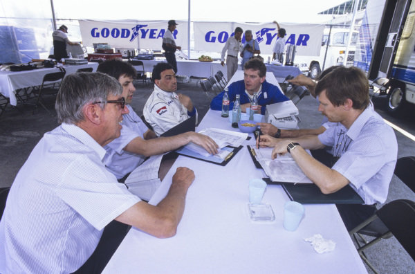 Ken Tyrrell leads a team briefing with drivers Michele Alboreto and Jonathan Palmer.