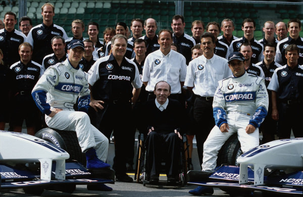 A Williams team photo. Ralf Schumacher and Juan Pablo Montoya sit on tyres. Frank Williams, Patrick Head, Gerhard Berger and Mario Theissen are grouped in the middle.