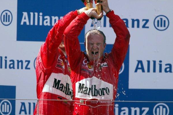 Race winner Rubens Barrichello (BRA) Ferrari celebrates on the podium with team mate Michael Schumacher (GER). European Grand Prix, Nurburgring, Germany, 23 June 2002. DIGITAL IMAGE