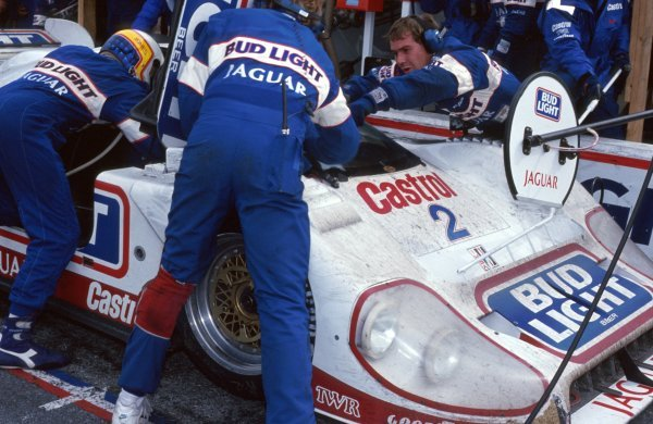 Davy Jones (USA) helps his team mate get into the TWR Jaguar XJR-12D during a pit stop.