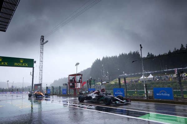 Sir Lewis Hamilton, Mercedes W12, leads Daniel Ricciardo, McLaren MCL35M, in the pit lane