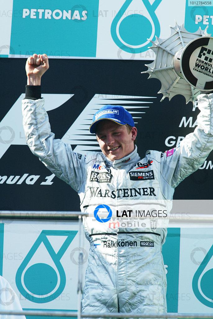 2003 Malaysian Grand Prix. Sepang, Kuala Lumpur, Malaysia.21-23 March 2003.Kimi Raikkonen (McLaren Mercedes) celebrates his 1st position and maiden Grand Prix win on the podium.World Copyright - LAT Photographic ref: Digital Image Only