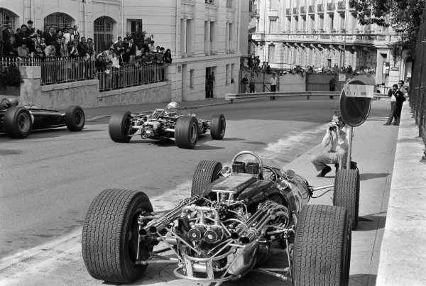 Denny Hulme, Brabham BT20 Repco, and Mike Spence, BRM P83, pass Dan Gurney's retired Eagle T1G Weslake, into Mirabeau corner.