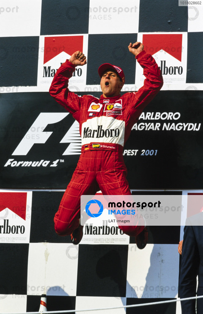 Michael Schumacher, 1st position, leaps on the podium in celebration as he secures the drivers' world championship for a fourth time.