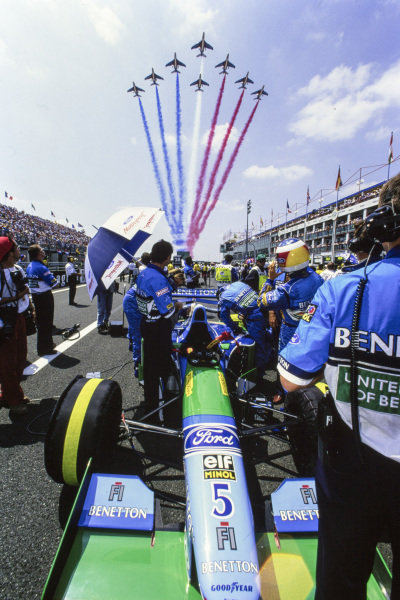 The French Air Force aerobatic team La Patrouille de France fly over the grid in their Dassault Alpha Jet trainers. Michael Schumacher, beside his Benetton B194 Ford, watches.