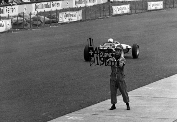 1965 German Grand Prix.Nurburgring, Germany. 1 August 1965.A Ferrari mechanic gives John Surtees a 4 seconnd lead over Dan Gurney and 19 seconds over Graham Hil, portrait.World Copyright: LAT PhotographicRef: B/W Print