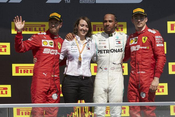 Sebastian Vettel, Ferrari, 2nd position, the Mercedes trophy delegate, Lewis Hamilton, Mercedes AMG F1, 1st position, and Charles Leclerc, Ferrari, 3rd position, on the podium