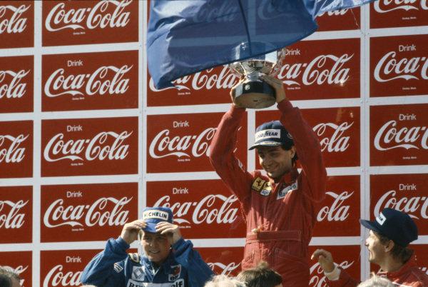 Michele Alboreto, 1st position, raises his trophy on the podium. Derek Warwick, 2nd position, and René Arnoux, 3rd position, are alongside.