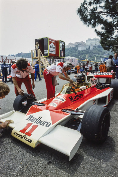 James Hunt sits in the paddock in his McLaren M23 Ford with Teddy Mayer.