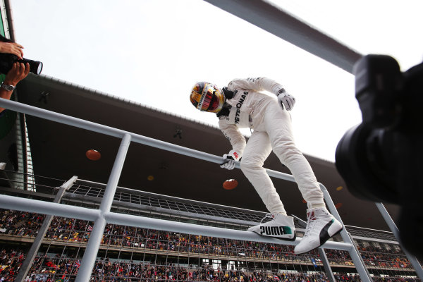 Shanghai International Circuit, Shanghai, China.  Saturday 08 April 2017.  Lewis Hamilton, Mercedes AMG, celebrates taking pole position by scaling a fence and interacting with fans. World Copyright: Charles Coates/LAT Images  ref: Digital Image AN7T9025