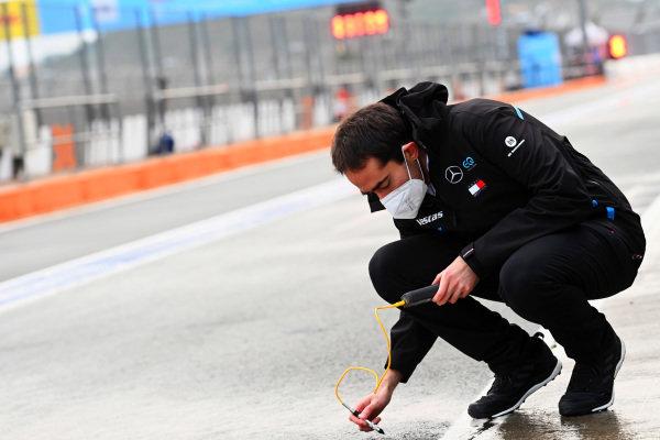 A Mercedes Benz EQ engineer checks the track temperature