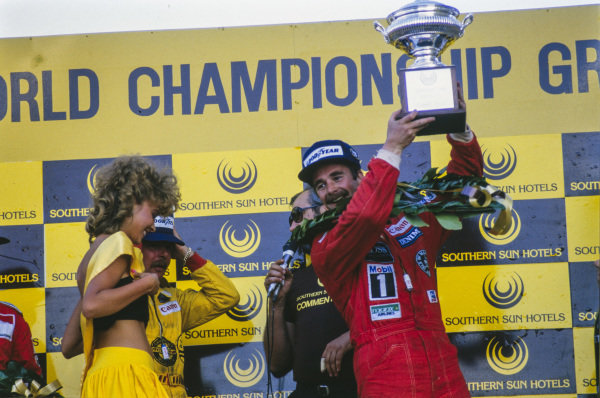 Nigel Mansell, 1st position, lifts his trophy on the podium.
