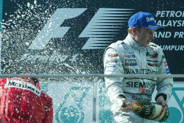 2003 Malaysian Grand Prix. Sepang, Kuala Lumpur, Malaysia.21-23 March 2003.Kimi Raikkonen (McLaren Mercedes) celebrates his 1st position and maiden Grand Prix win on the podium, with the champagne.World Copyright - LAT Photographic ref: Digital Image Only