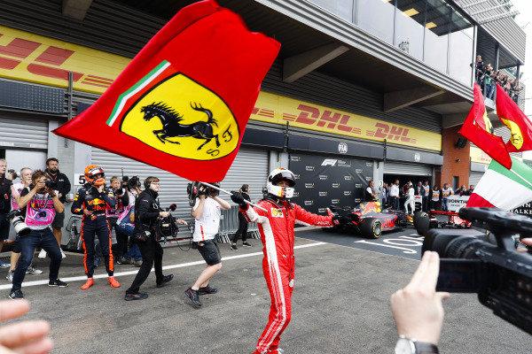 Sebastian Vettel, Ferrari, celebrates victory in parc ferme, as Max Verstappen, Red Bull Racing, looks on.
