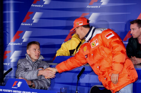 2000 British Grand Prix.Silverstone, England.21-23 April 2000.Mika Hakkinen (McLaren Mercedes) greets Michael Schumacher (Ferrari) as he arrives at a press conference.World Copyright - Steve Etherington/LAT Photographic18mb Digital