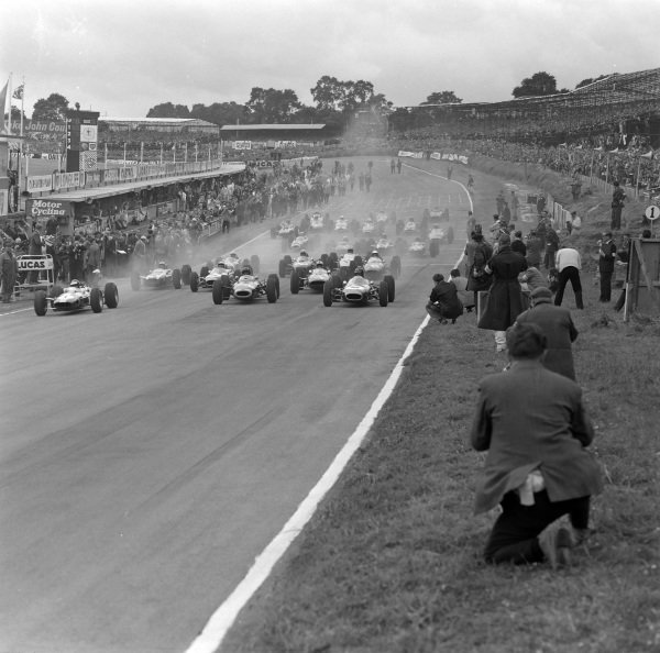 The start of the race, with Jim Clark, Lotus 25 Climax, battling against Graham Hill, BRM P261, and Dan Gurney, Brabham BT7 Climax, off the line.