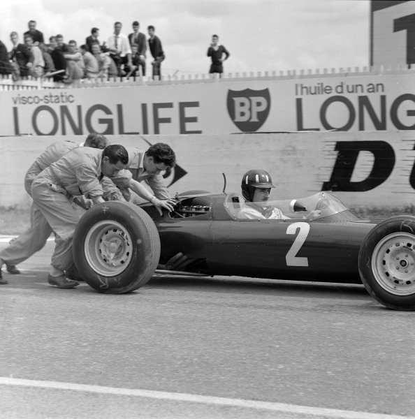 Graham Hill, BRM P61, is pushed by mechanics.