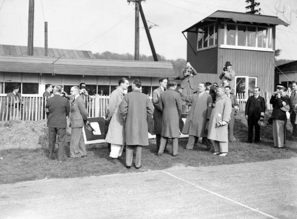 Richard Seaman (goggles around neck) speaks with HRH Duke of Kent (back to camera), President-in-chief of the BRDC, while Adolf Huhnlein, head of the NSKK, stands on the right (with binoculars around neck).