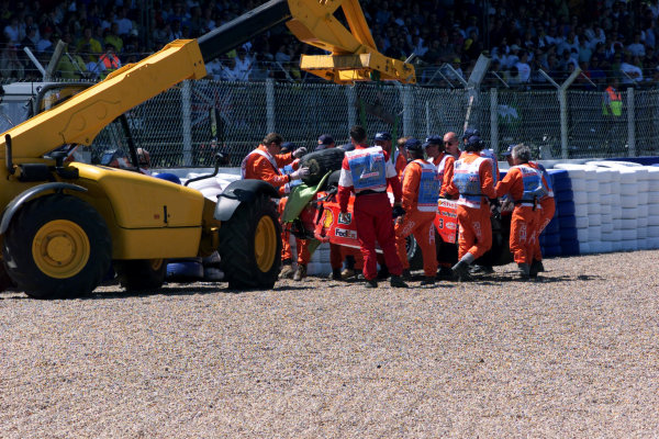 1999 British Grand Prix. Silverstone, England. 9th - 11th July 1999. Marshals remove the wrecked Ferrari F399 after Michael Schumacher had crashed heavily into the tyre barriers at Stowe on the first lap, breaking his leg. World Copyright: LAT Photographic.  Ref:  99_GB_MS_Crash_09.