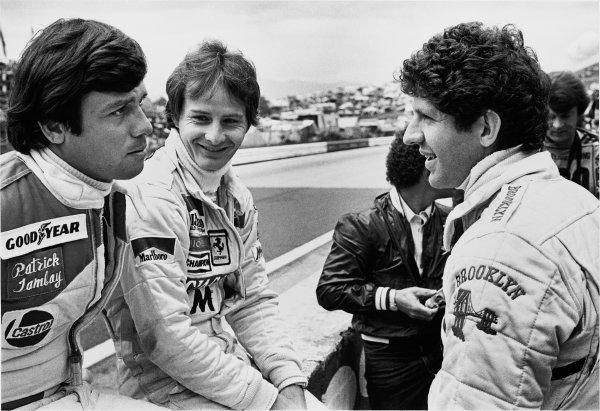 Osterreichring, Zeltweg, Austria. 10-12 August 1979. Gilles Villeneuve (Ferrari 312T4) chats with team mate Jody Scheckter (Ferrari 312T4) and Patrick Tambay (McLaren M29) in the pits, portrait. World Copyright - LAT Photographic. ref: 12848/15.