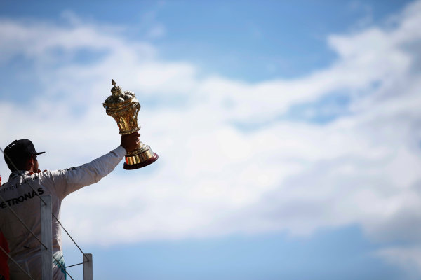 Silverstone Circuit, Northamptonshire, England. Sunday 5 July 2015. Lewis Hamilton, Mercedes AMG, 1st Position, lifts his trophy. World Copyright: Glenn Dunbar/LAT Photographic ref: Digital Image _89P4180
