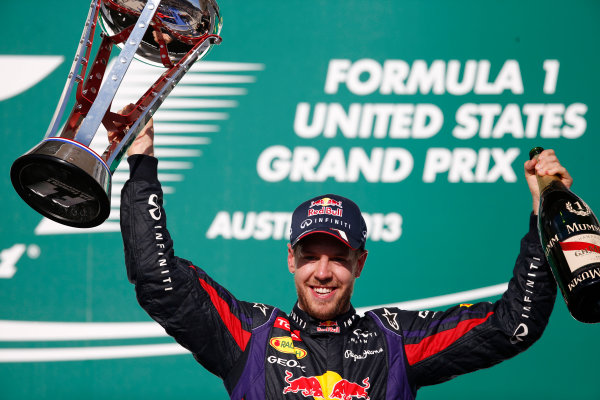 Circuit of the Americas, Austin, Texas, United States of America. Sunday 17th November 2013.  Sebastian Vettel, Red Bull Racing, 1st position, celebrates on the podium with his trophy and Champagne. World Copyright: Glenn Dunbar/LAT Photographic. ref: Digital Image _89P0962