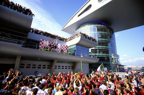 Fans swarm the track to watch the podium ceremony.