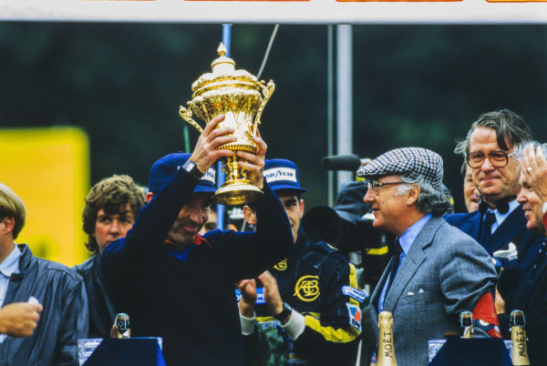 Frank Williams lifts the trophy awarded to the winning constructor on the podium.