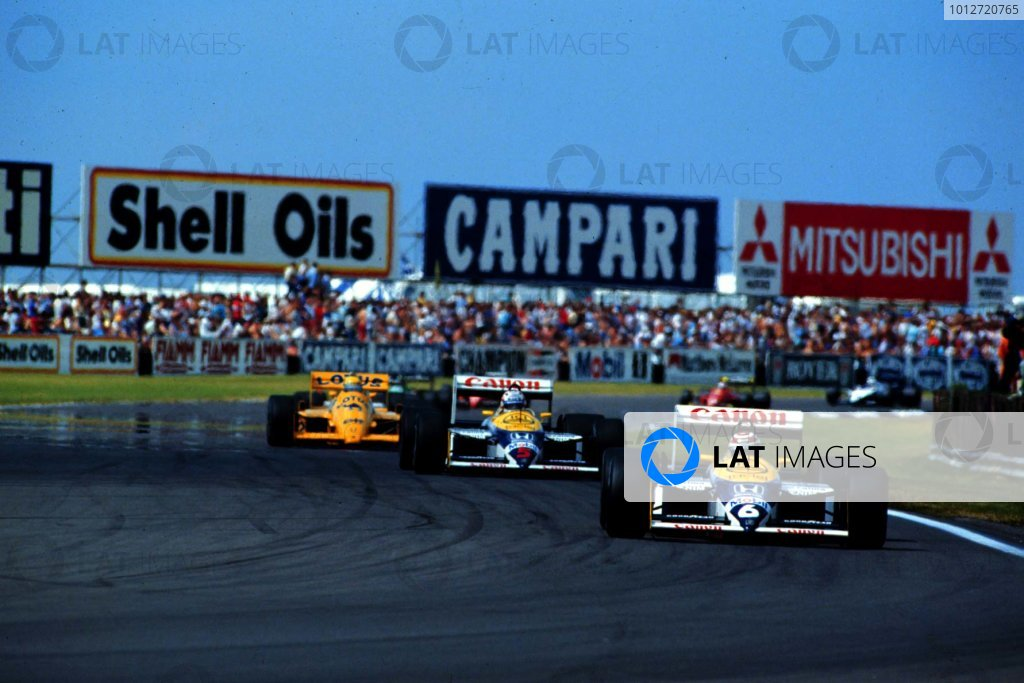 1987 British Grand Prix.Silverstone, England.10-12 July 1987.Nelson Piquet leads Nigel Mansell (both Williams FW11B Honda) and Ayrton Senna (Lotus 99T Honda) at the start. They finished in 2nd, 1st and 3rd positions respectively.  Ref: 87GB27. World Copyright - LAT Photographic