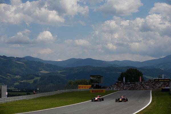 Red Bull Ring, Spielberg, Austria. Sunday 22 June 2014. Daniel Ricciardo, Red Bull Racing RB10 Renault, passes Jules Bianchi, Marussia MR03 Ferrari. World Copyright: Glenn Dunbar/LAT Photographic. ref: Digital Image _W2Q1874