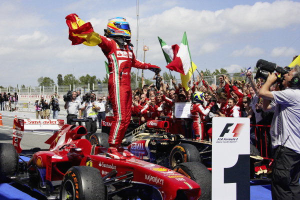 Fernando Alonso stands on his Ferrari F138 as he celebrates victory in parc ferme.