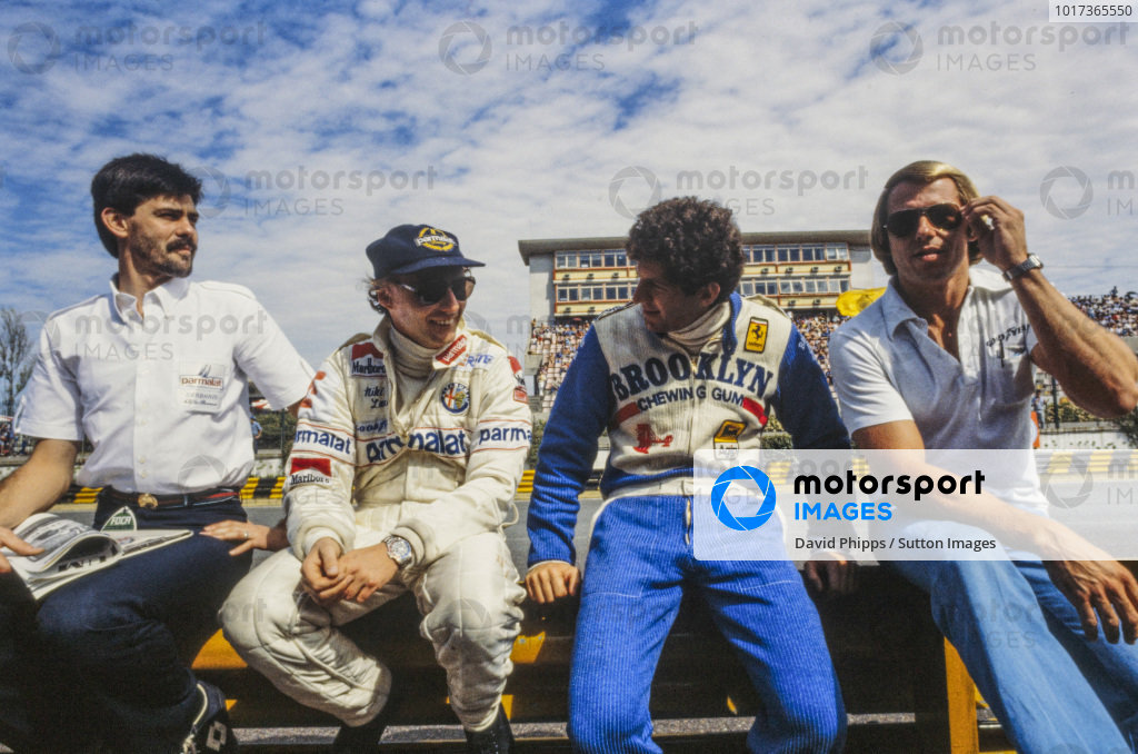 Niki Lauda and Jody Scheckter sit together on the pit wall. Brabham designer Gordon Murray is seated on the left.
