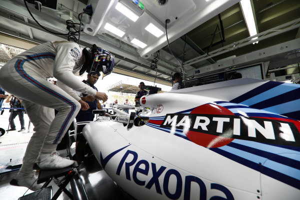 Lance Stroll, Williams Racing, enters his cockpit in the team's garage.