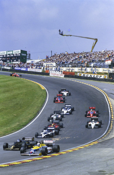 Nigel Mansell, Williams FW11 Honda, leads Johnny Dumfries, Lotus 98T Renault, Derek Warwick, Brabham BT55 BMW, Michele Alboreto, Ferrari F1/86, Martin Brundle, Tyrrell 015 Renault, Teo Fabi, Benetton B186 BMW, Alan Jones, Lola THL-2 Ford, and Riccardo Patrese, Brabham BT54 BMW, through Paddock Hill Bend.