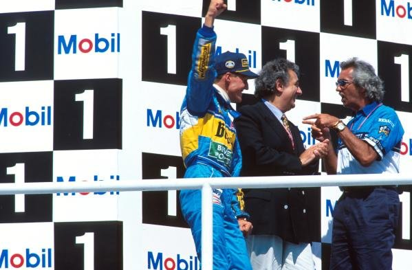 Opera singer, Placido Domingo, centre, joins Michael Schumacher and Flavio Briatore on the podium. German GP, Hockenheim, 30 July 1995
