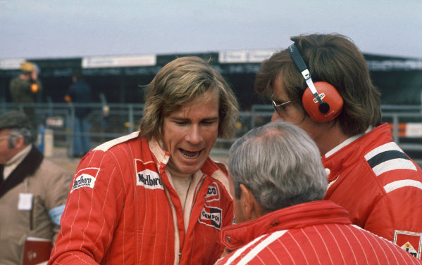 Silverstone, Great Britain. 11th April 1976. James Hunt (McLaren M23-Cosworth), 1st position, talks to Alastair Caldwell and Teddy Mayer in the pits, portrait.  World Copyright: LAT Photographic.  Ref:  76 INT 05.