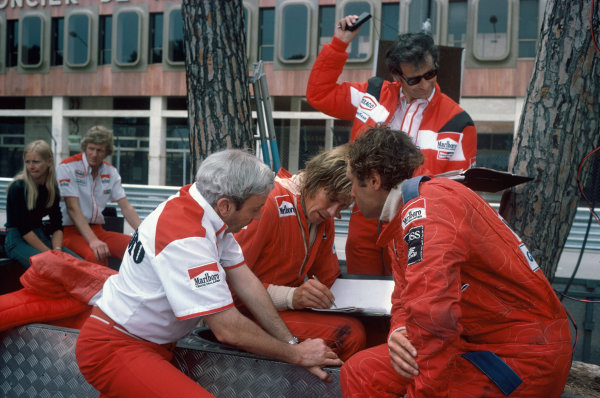 Monte Carlo, Monaco. 30th May 1976. Teddy Mayer, James Hunt and Jochen Mass (McLaren M23-Ford) looking at practice times in the pit lane, portrait.  World Copyright: LAT Photographic.  Ref:  76 MON 50.