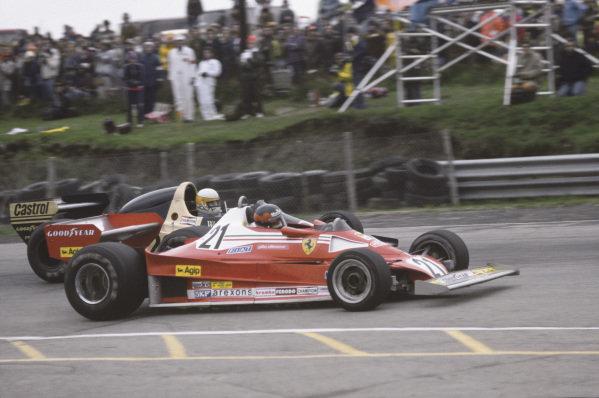 Mosport Park, Ontario, Canada.7 Gilles Villeneuve (Ferrari 312T2), 12th position, passes Jody Scheckter (Wolf WR1-Ford), 1st position, action. World Copyright:c Ref:  77CAN25.