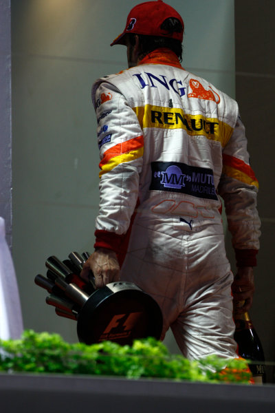 Marina Bay Circuit, Singapore. 27th September 2009. Fernando Alonso, Renault R29, 3rd position, leaves the podium with his trophy. Portrait. Podium.  World Copyright: Andrew Ferraro/LAT Photographic ref: Digital Image _H0Y0893