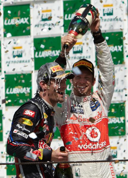 Interlagos, Sao Paulo, Brazil. 27th November 2011. Mark Webber, Red Bull Racing RB7 Renault, 1st position, gets a soaking from Jenson Button, McLaren MP4-26 Mercedes, 3rd position. Portrait. Podium.  World Copyright: Steve Etherington/LAT Photographic ref: Digital Image SNE28383