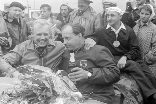 Mike Hawthorn and Ivor Bueb, 1st position, celebrate victory in the cockpit of their Jaguar D-type after the race.