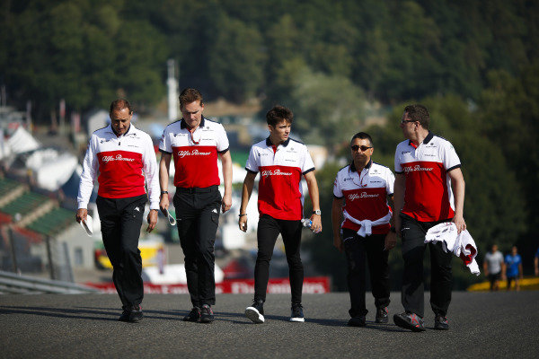 Charles Leclerc, Alfa Romeo Sauber F1 Team, walks the circuit with colleagues.
