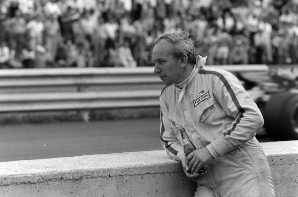 John Surtees watches the on track action after retiring from the race.